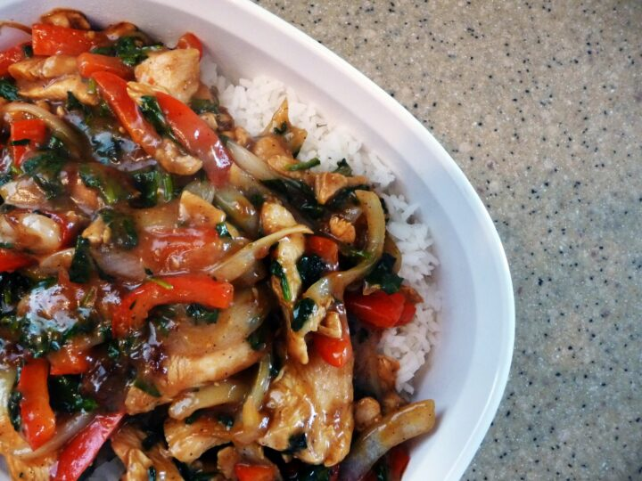 Chicken and pepper stir fry over rice on a white plate.