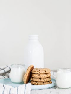 stack of cookies on plate with 2 glasses milk