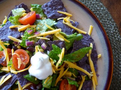 Overhead view of a veggie black bean taco salad on a plate.