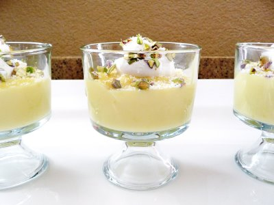 Three glass dishes filled with homemade white chocolate pudding and garnished with pistachios and whipped cream.