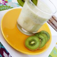 A pineapple orange smoothie in a glass, on an orange plate with kiwi slices.