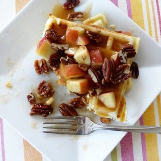 waffles on a white plate with syrup, apples, and pecans
