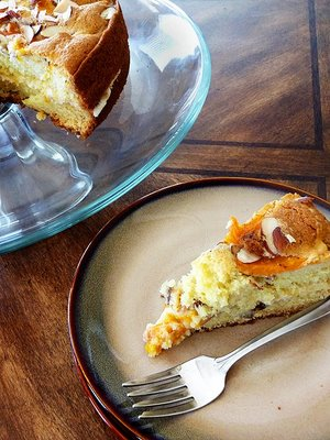 A slice of apricot almond cake on a dessert plate, next to a cake stand with the rest of the cake.