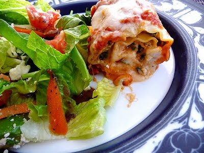 A spinach lasagna roll on a plate with a side salad.