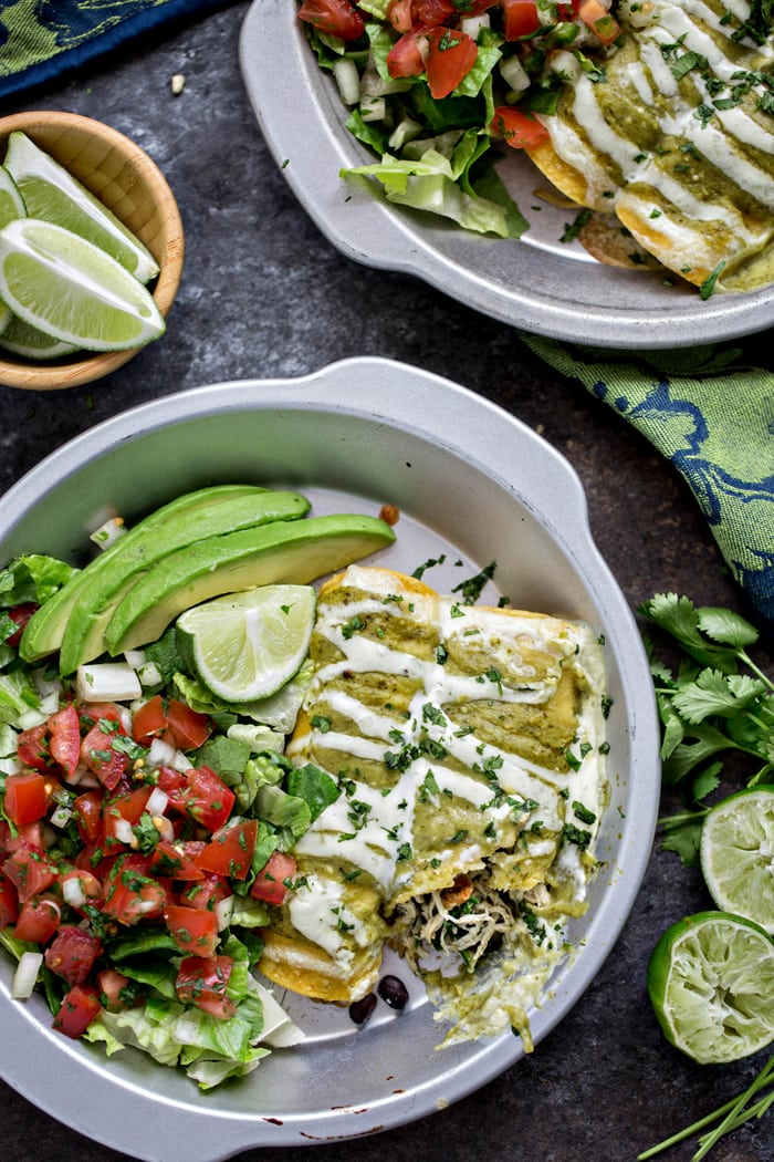 spinach enchiladas in round pan, drizzled with sour cream and tomatillo sauce