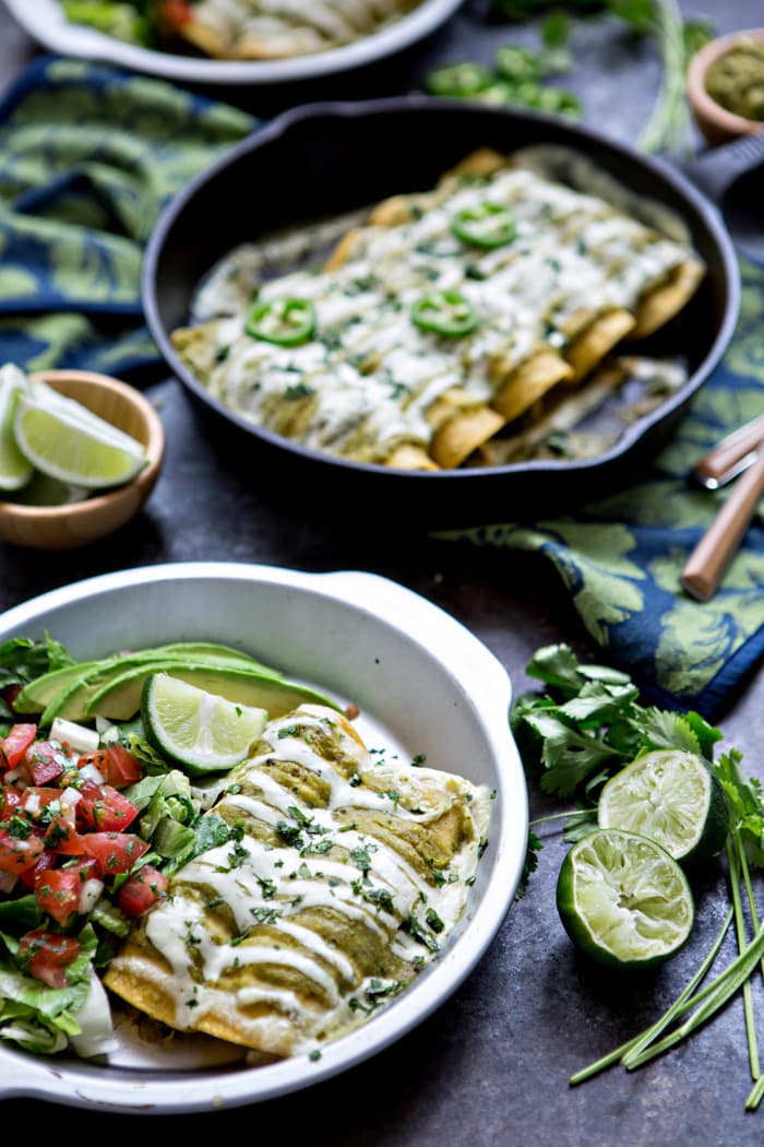 green enchiladas smothered in sour cream sauce and tomatillo sauce