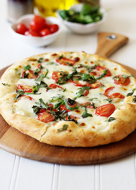A pizza caprese with focaccia crust on a wooden pizza peel.