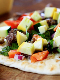 flat bread pizza with zucchini, sausage, peppers, and basil