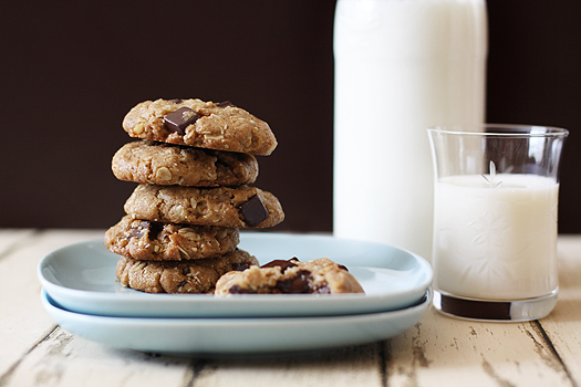 A stack of chocolate chip almond butter oatmeal cookies on a blue plate, next to a jug and glass of milk.