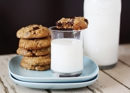 Oatmeal almond butter chocolate chip cookies on a blue plate with a glass of milk. One cookie rests on the rim of the glass.