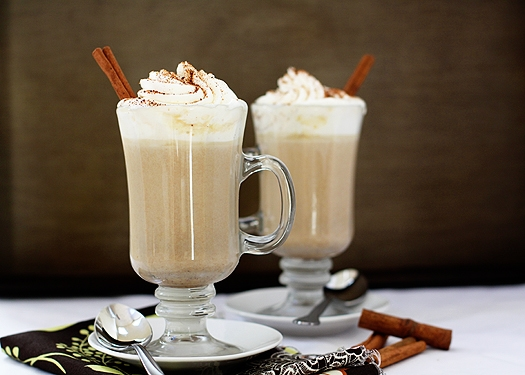 two glasses of homemade white hot chocolate garnished with cinnamon sticks and whipped cream