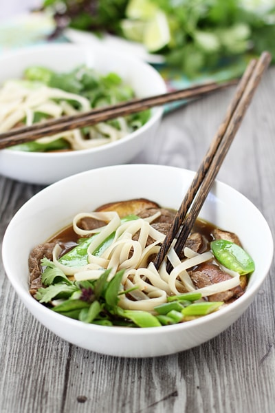 vietnamese rice noodle soup in white bowl with chopsticks