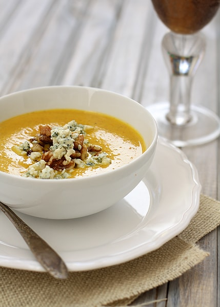 A bowl of canned pumpkin soup garnished with walnuts and blue cheese.