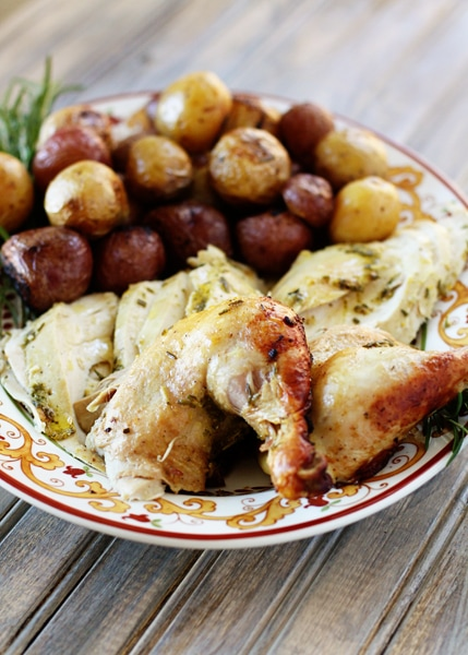 rosemary roasted chicken pieces on a plate with roasted potatoes