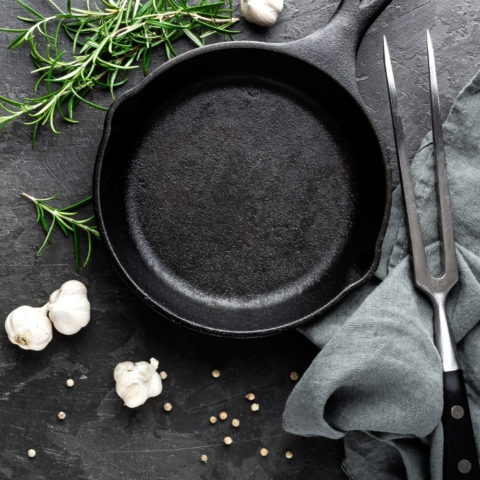 overhead shot of a cast iron pan with herbs and garlic