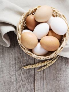 a basket of eggs on a table with cloth
