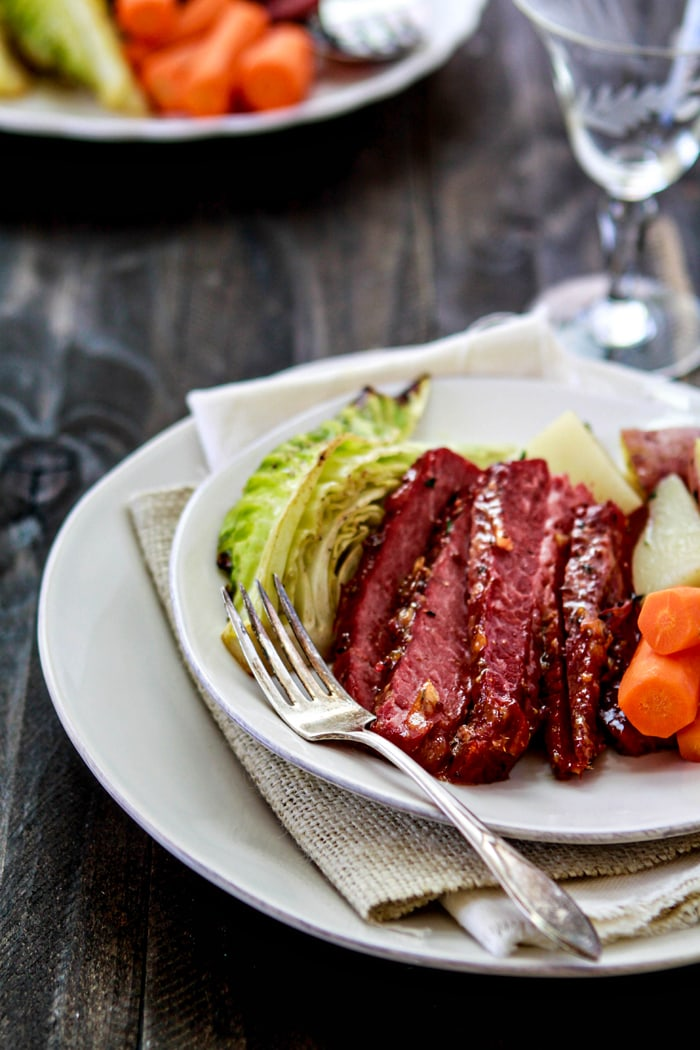 sliced glazed corned beef on plate with vegetables