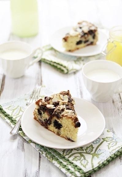 Two slices of lemon blueberry coffee cake on white plates.
