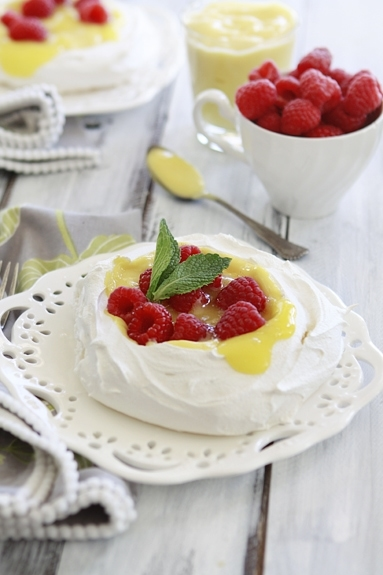 lemon curd pavlova topped with raspberries