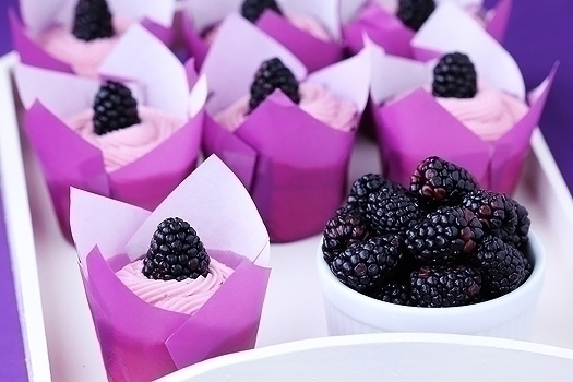 easy lemon cupcakes topped with blackberry buttercream frosting in paper liners