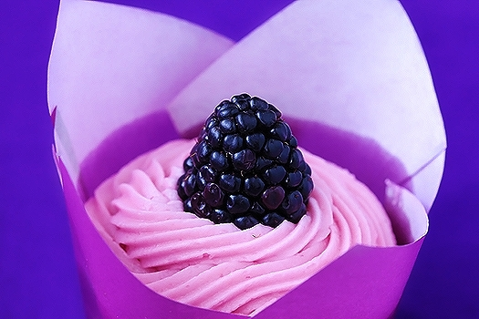 A lemon cupcake with blackberry frosting in a liner