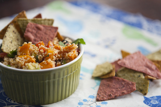 Mexican sweet potato quinoa salad in a green dish with tortilla chips