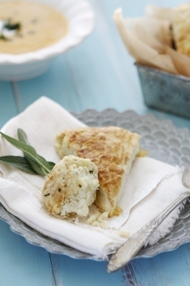 A savory scone on a white napkin that's laid over a small plate.