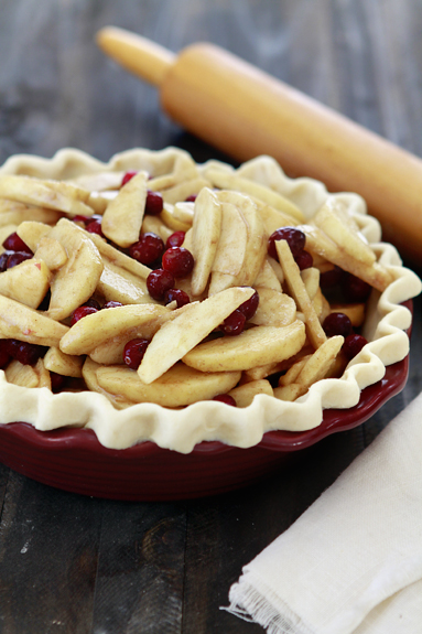 all butter pie crust in pie plate filled with apples and cranberries