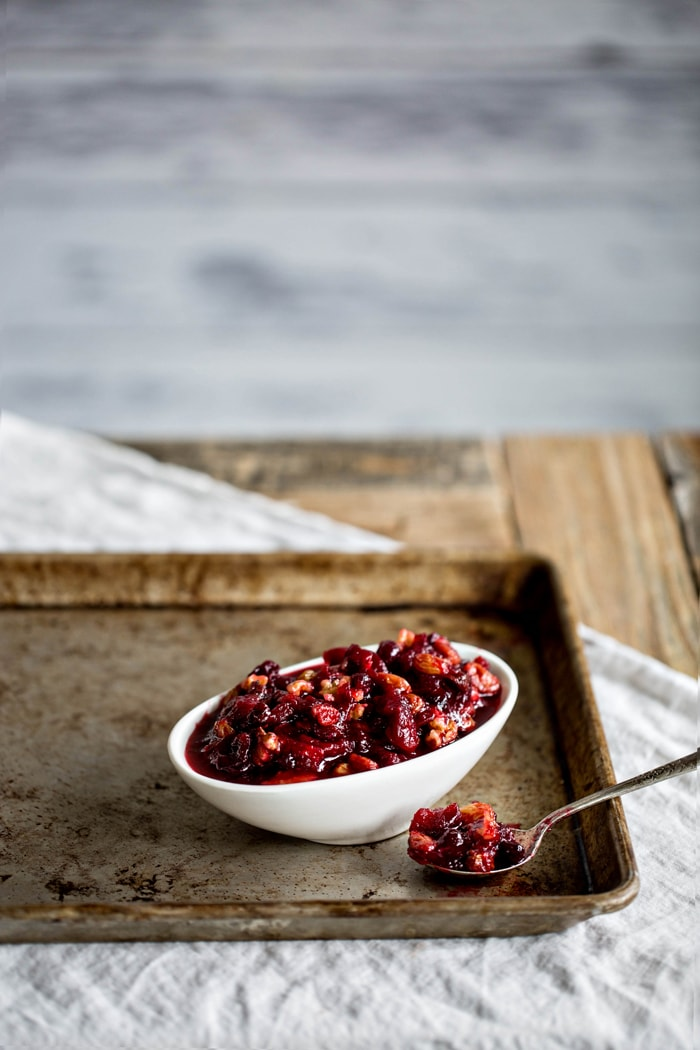 cranberry sauce with orange juice in white serving dish next to spoon