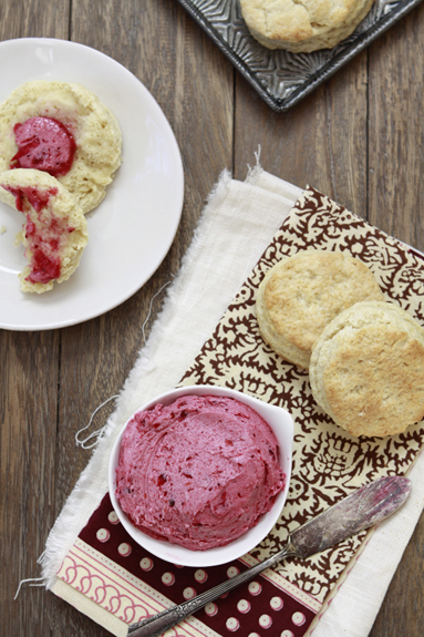 Overhead view of a bowl of whipped cranberry butter next to two biscuits. Additional biscuits are on a white plate.