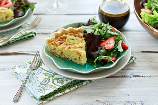 slice of quiche lorraine on blue plate with salad