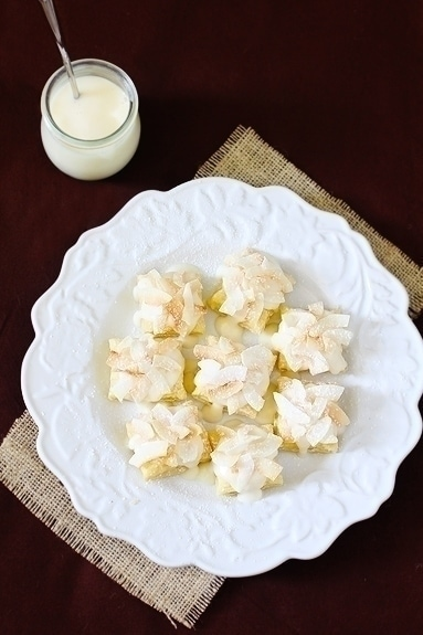 """Coconut Cream Cheese Pastry Bites   These """"bites"""" are just just simple little squares (or you could make them larger squares or circles) of puff pastry, topped with a coconut cream cheese sauce, and then garnished with toasted coconut."""