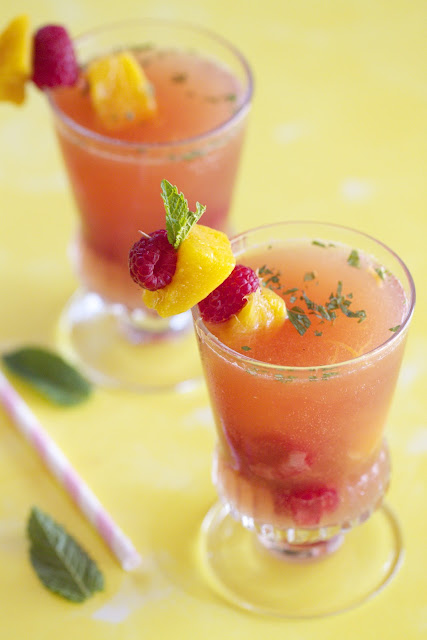 Two raspberry mango sangrias in a glasses garnished with fresh fruit and mint.