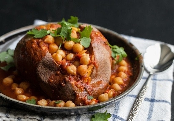 A slightly spicy chickpea and tomato stew served over a sweet potato. Spiced Chickpea Smothered Sweet Potato are an easy and hearty vegetarian meal that is perfect for winter.