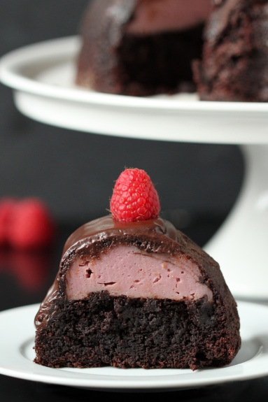 A slice of chocolate cake with raspberry filling on a plate. The rest of the bundt cake rests in the background.