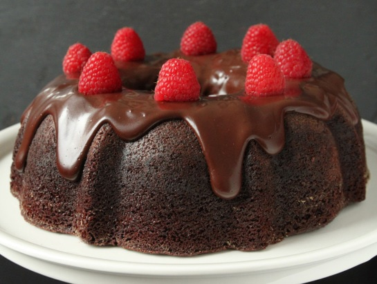 A chocolate raspberry bundt cake topped with ganache and fresh berries