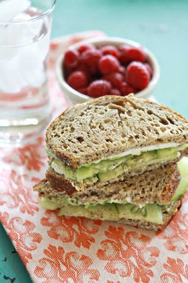 Cucumber and Avocado Sandwich sliced and stacked in front of a bowl of raspberries