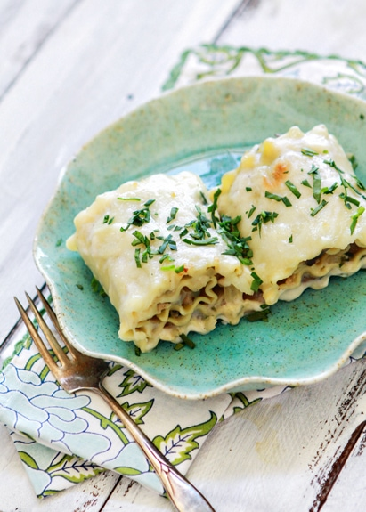 Two chicken lasagna rolls ups on a blue plate