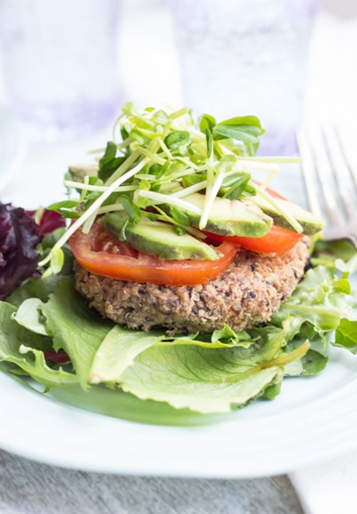 Black Bean Quinoa Burger on lettuce leaf with vegetarian toppings