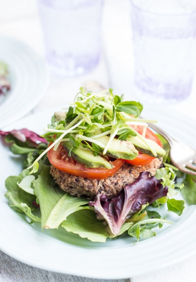 Black Bean Quinoa Burger patty on lettuce with sliced tomato and greens on top