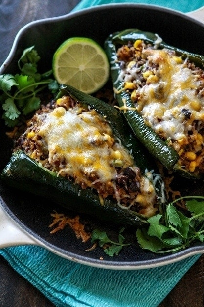 These Shredded Beef, Black Bean and Quinoa Stuffed Poblanos are a healthier take on Chile Rellanos. The poblanos are roasted instead of friend, and they are stuffed with  a mixture of Mexican shredded beef, quinoa, black beans, and corn.