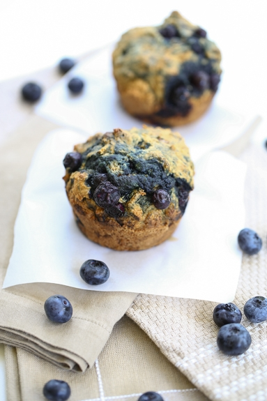 two healthy blueberry muffins on napkins