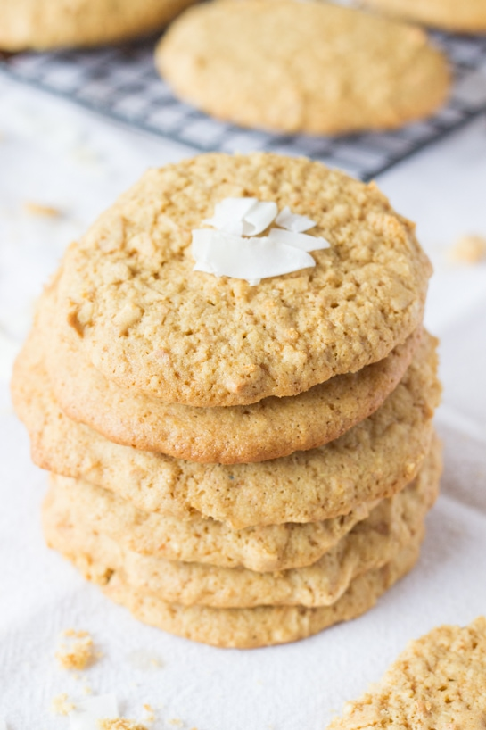 A stack of toasted coconut cookies, garnished with coconut flakes.