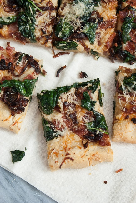 Overhead view of a sliced caramelized onion and bacon pizza.