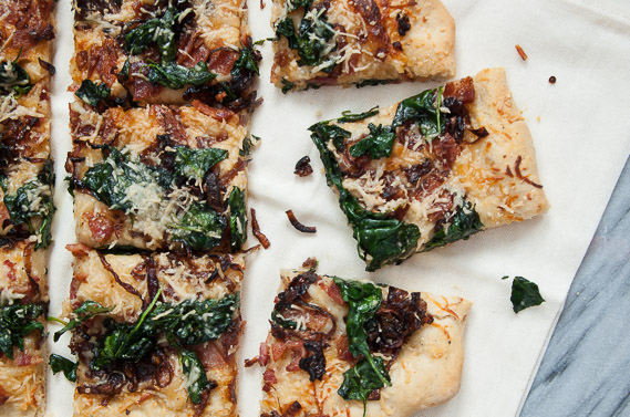 Caramelized Onion, Spinach, and Bacon Pizza   Delicious homemade pizza with the amazing flavors of a garlic cream sauce, caramelized red onions, crispy bacon and sauteed spinach.