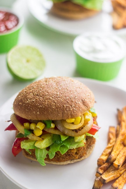 A sweet potato veggie burger on a plate with fries.