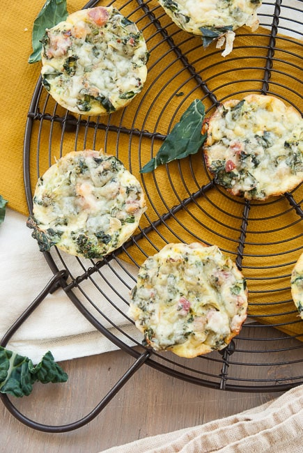 Overhead view of crustless broccoli cheese quiche muffins on a wire cooling rack.