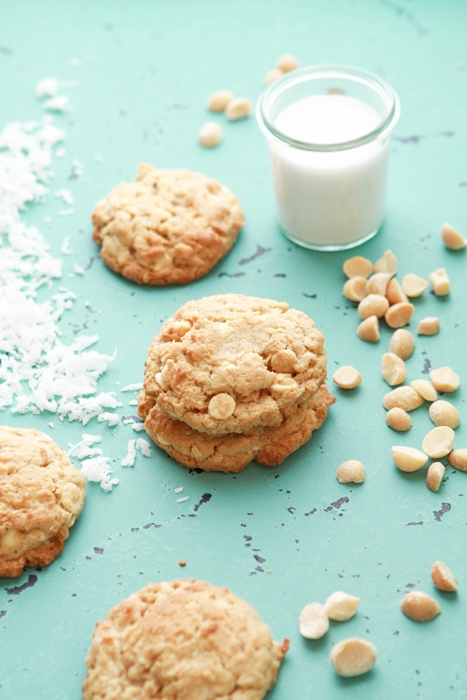 White chocolate lemon coconut cookies on a bright blue background, next to a glass of milk.