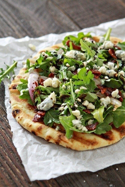 A grilled flatbread pizza topped with bacon, blue cheese, and arugula.