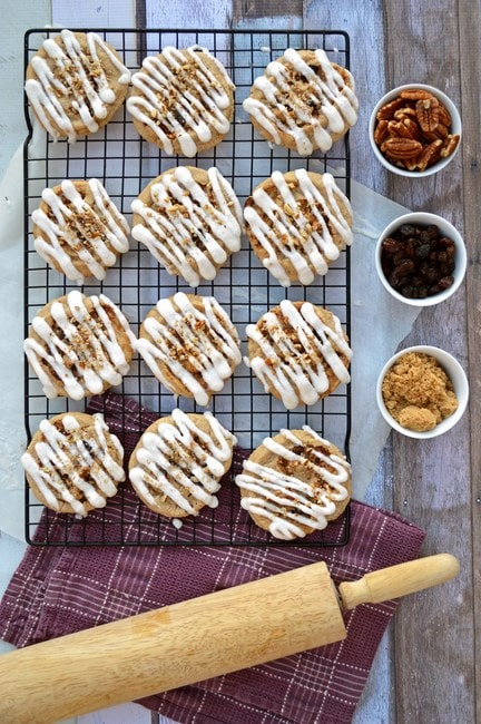 Overhead view of cinnamon roll cookies on a wire rack. Small bowls of pecans, raisins, and brown sugar lay nearby, as does a wood rolling pin.